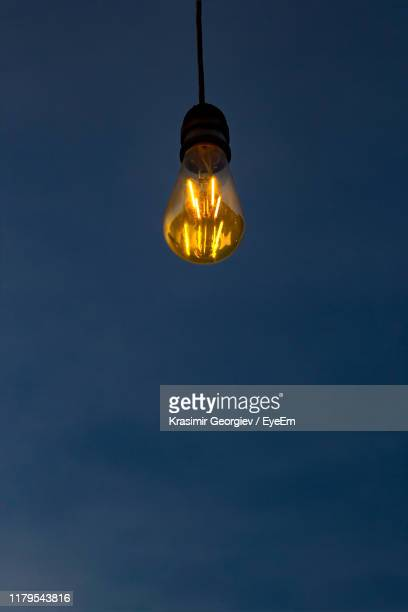 low angle view of illuminated light bulb against blue sky - krasimir georgiev stock photos and pictures