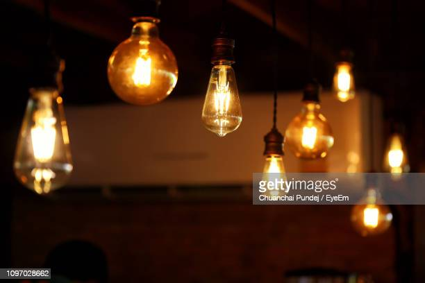 low angle view of illuminated light bulb hanging from ceiling - pendant light stock pictures, royalty-free photos & images