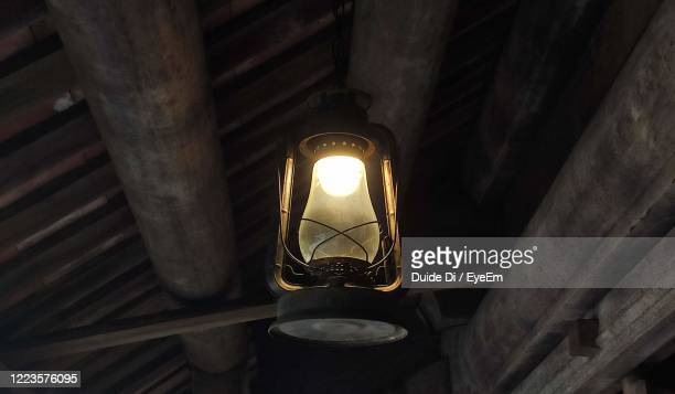 low angle view of illuminated light bulb hanging from ceiling - ガス燈 ストックフォトと画像
