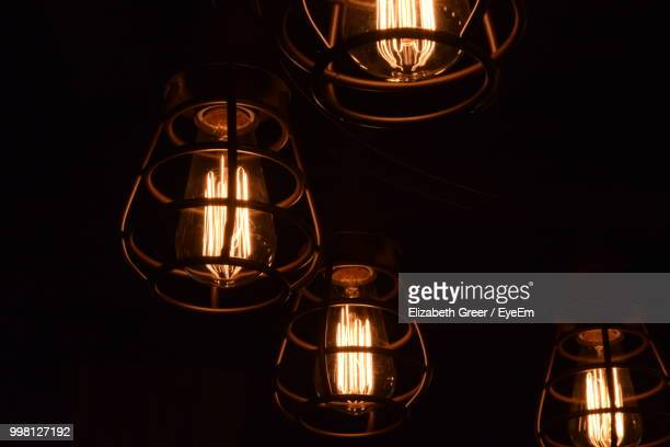 Low Angle View Of Illuminated Light Bulb In Darkroom