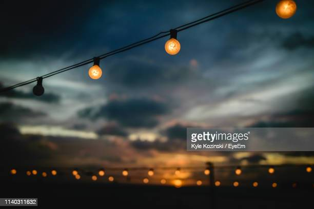 low angle view of illuminated light bulbs against sky at sunset - oranjestad stockfoto's en -beelden