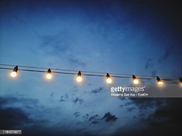 low angle view of illuminated light bulbs against sky - 隣り合わせ ストックフォトと画像