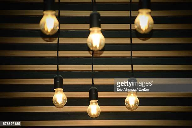 Low Angle View Of Illuminated Light Bulbs Against Wall