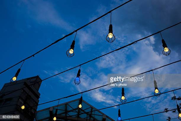 Low Angle View Of Illuminated Light Bulbs Hanging Against Sky