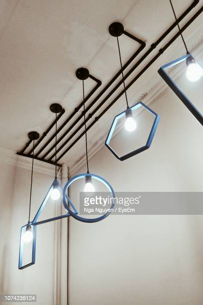low angle view of illuminated light bulbs hanging from ceiling - nga nguyen stock pictures, royalty-free photos & images