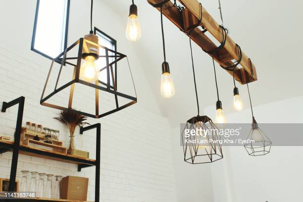 low angle view of illuminated light bulbs hanging from ceiling - pendant light stock pictures, royalty-free photos & images