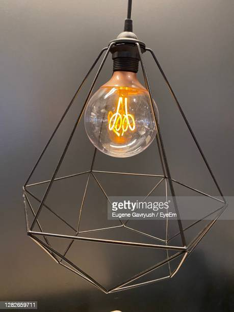 low angle view of illuminated light bulbs hanging from ceiling - フィラメント ストックフォトと画像