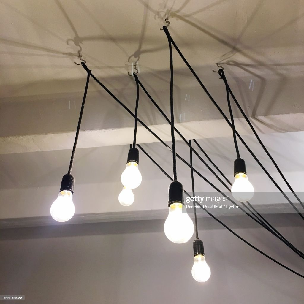 Low Angle View Of Illuminated Light Bulbs Hanging On Ceiling : Stock Photo
