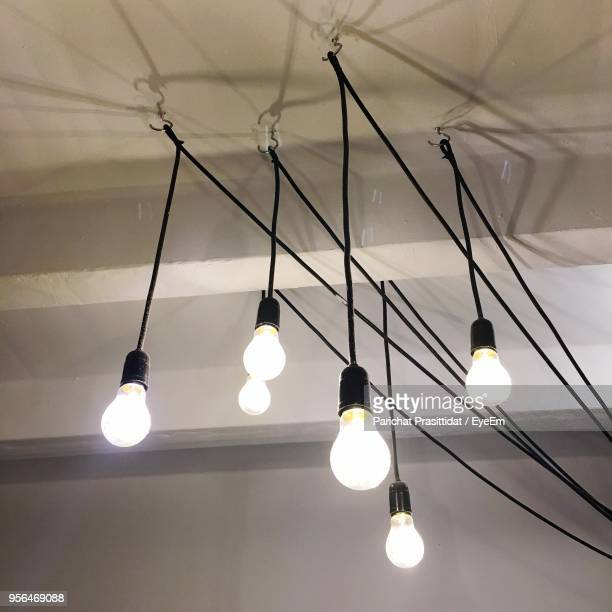 Low Angle View Of Illuminated Light Bulbs Hanging On Ceiling