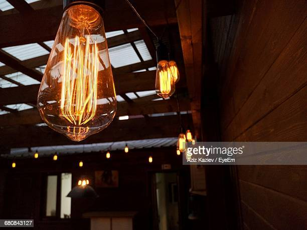 Low Angle View Of Illuminated Light Bulbs In Restaurant