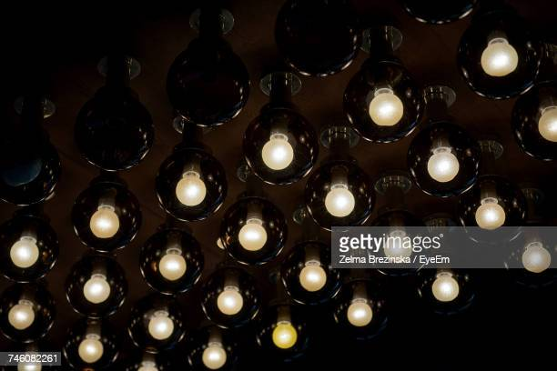 Low Angle View Of Illuminated Light Bulbs On Ceiling