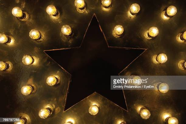 low angle view of illuminated light bulbs on ceiling - gold star stock pictures, royalty-free photos & images