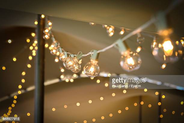 Low Angle View Of Illuminated Light Bulbs On String During Party