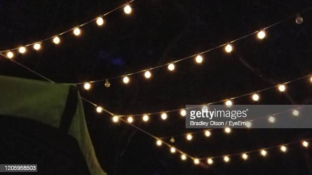 low angle view of illuminated light bulbs - hanging stock pictures, royalty-free photos & images