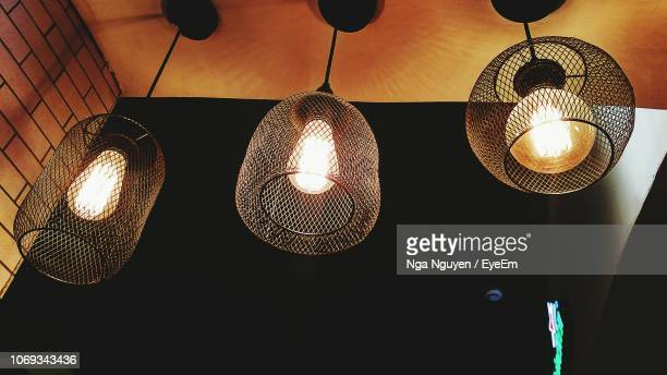 low angle view of illuminated light fixtures hanging from ceiling - nga nguyen stock pictures, royalty-free photos & images