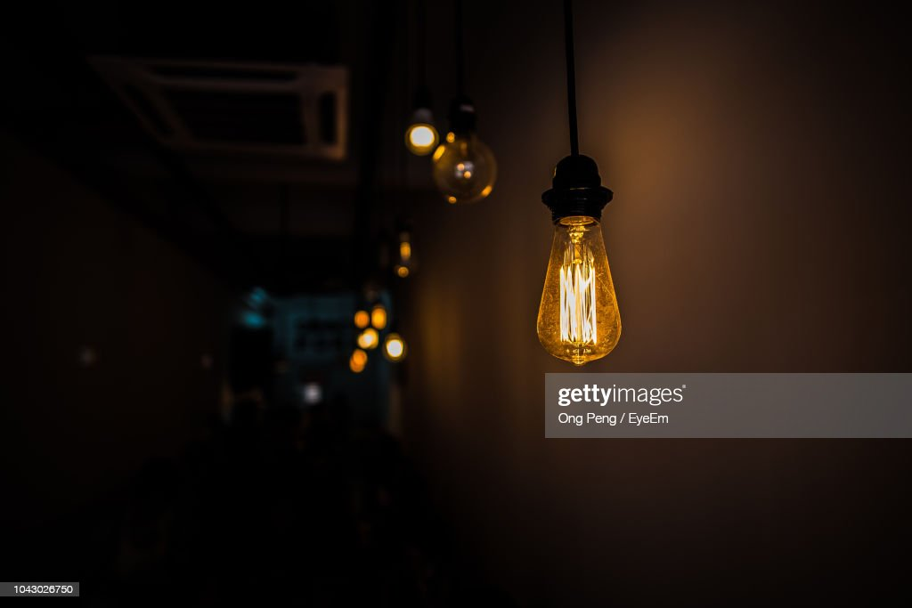 Low Angle View Of Illuminated Light Hanging Against Wall In Darkroom : Stock Photo