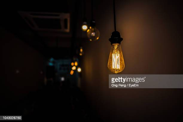 low angle view of illuminated light hanging against wall in darkroom - lamp stock photos and pictures