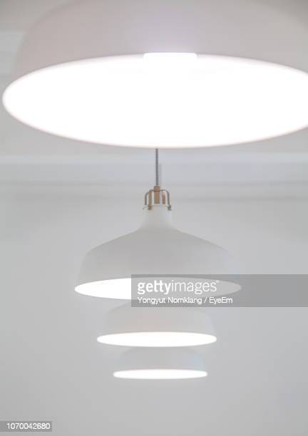 low angle view of illuminated lighting equipment in row - pendant light stock pictures, royalty-free photos & images