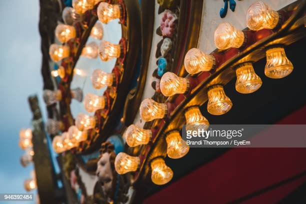 low angle view of illuminated lighting equipment on decoration - traveling carnival stock pictures, royalty-free photos & images