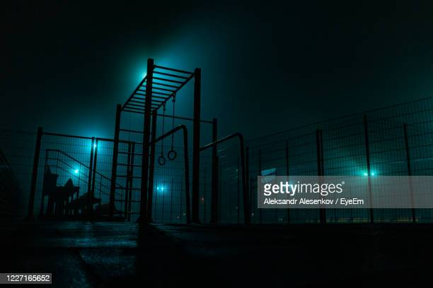 low angle view of illuminated lights by fence against sky at night - light natural phenomenon stock pictures, royalty-free photos & images