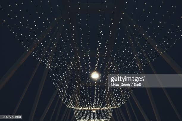 low angle view of illuminated lights hanging from ceiling - ソルナ ストックフォトと画像