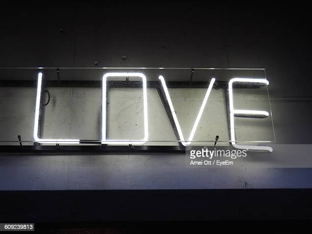 Low Angle View Of Illuminated Love Text On Wall At Night