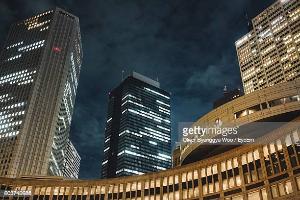 Low Angle View Of Illuminated Modern Buildings Against Cloudy Sky At Night
