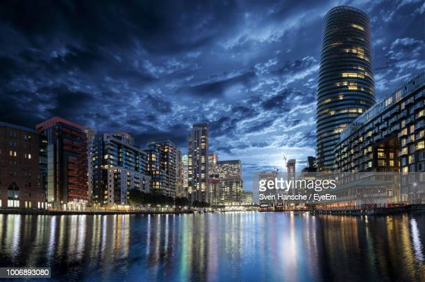 low angle view of illuminated modern buildings by river in city against sky at night - isle of dogs london stock pictures, royalty-free photos & images
