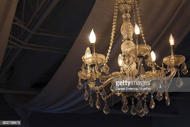 Low Angle View Of Illuminated Old Chandelier Hanging Against Fabric