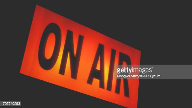 Low Angle View Of Illuminated On Air Sign Against Black Background