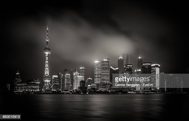 Low Angle View Of Illuminated Oriental Pearl Tower Amidst Buildings In Front Of River At Night