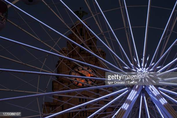 low angle view of illuminated panoramic wheel at night - liverpool england stock pictures, royalty-free photos & images