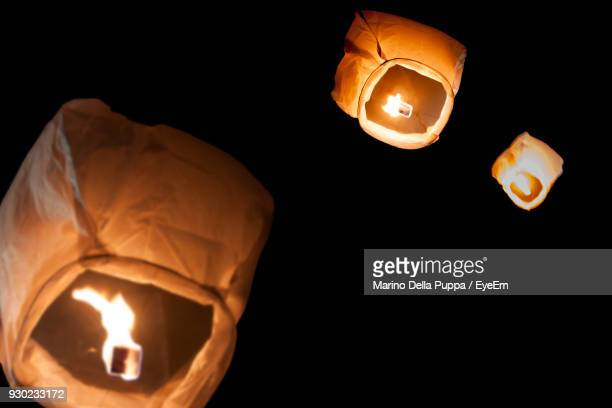 Low Angle View Of Illuminated Paper Lanterns Flying Against Clear Sky At Night