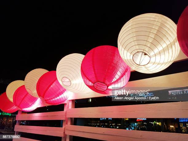 Low Angle View Of Illuminated Paper Lanterns On Wooden Railing