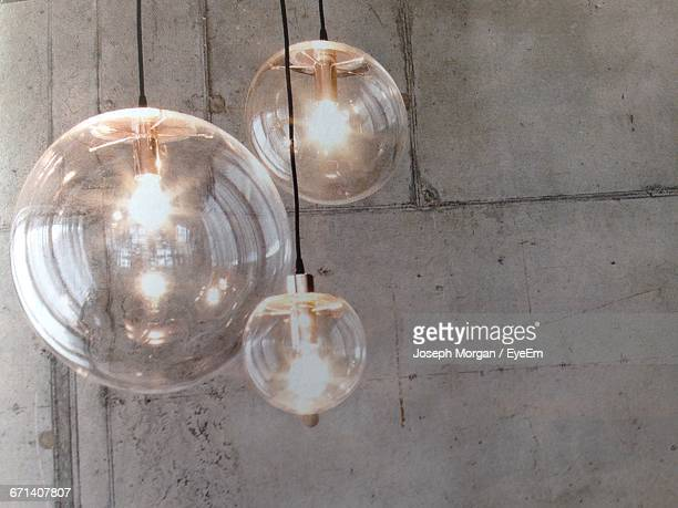 Low Angle View Of Illuminated Pendant Light Against Wall