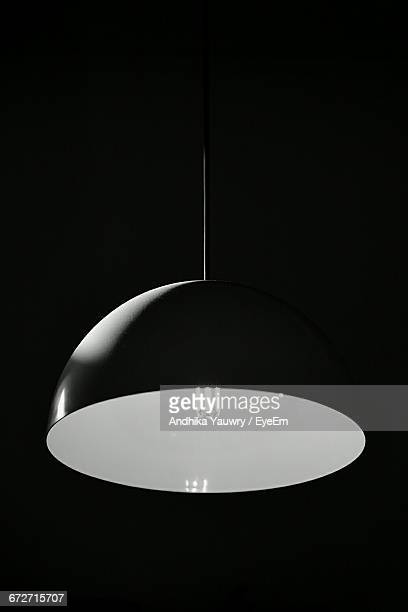 Low Angle View Of Illuminated Pendant Light Hanging Against Black Background