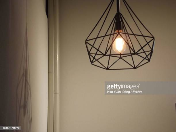 Low Angle View Of Illuminated Pendant Light Hanging Against Wall