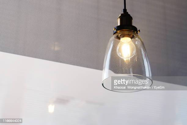 low angle view of illuminated pendant light hanging from ceiling - pendant light stock pictures, royalty-free photos & images