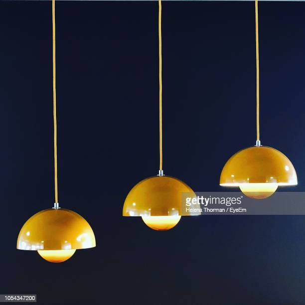 low angle view of illuminated pendant lights hanging against black background - pendant light stock pictures, royalty-free photos & images