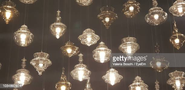 Low Angle View Of Illuminated Pendant Lights Hanging In Darkroom