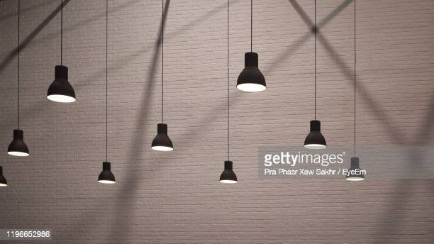low angle view of illuminated pendant lights hanging on ceiling - pendant light stock pictures, royalty-free photos & images