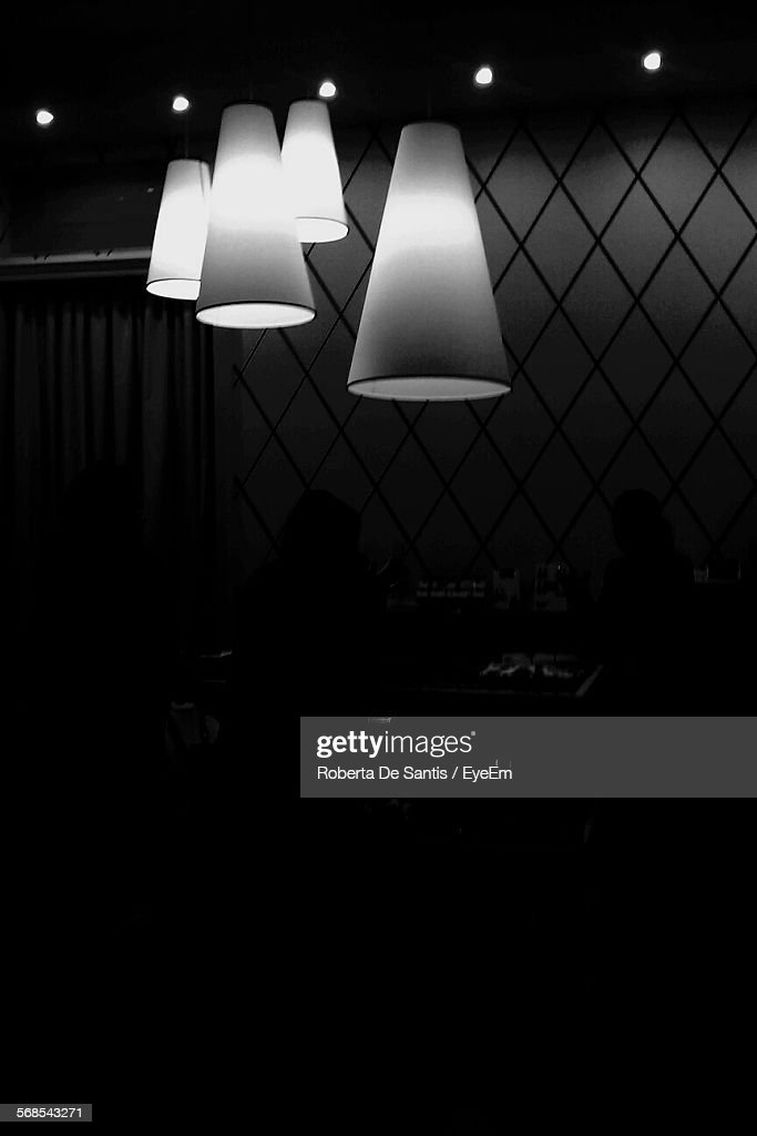 Low Angle View Of Illuminated Pendant Lights In Darkroom : Stock Photo