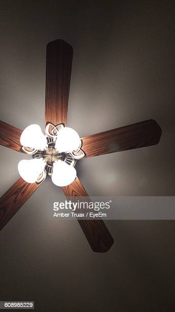 Low Angle View Of Illuminated Pendant Lights On Ceiling Fan At Home