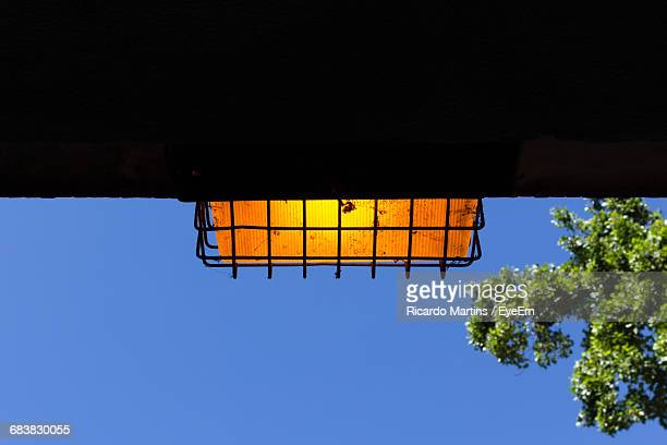 Low Angle View Of Illuminated Recessed Light On Silhouette Wall Against Clear Blue Sky