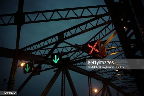 low angle view of illuminated road signals against sky at night - wegweiser stock-fotos und bilder