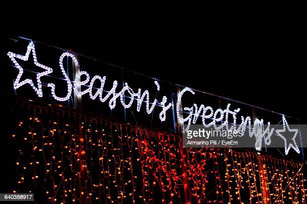 low angle view of illuminated seasons greetings against clear sky - stars and strings stock photos and pictures