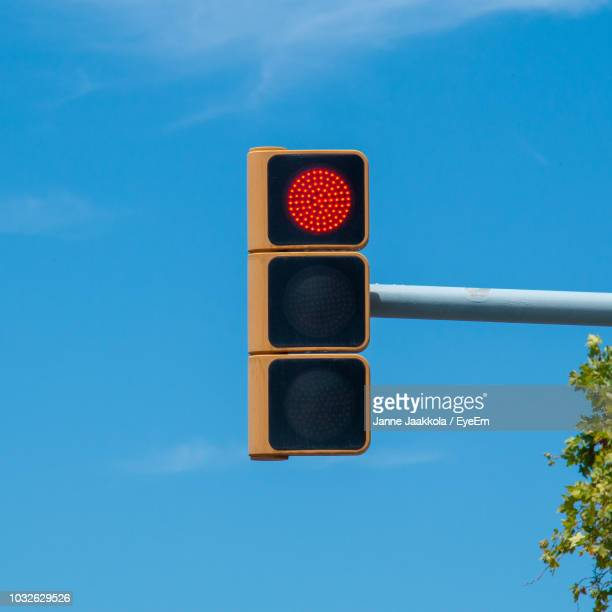 low angle view of illuminated signal light against blue sky - red light stock pictures, royalty-free photos & images