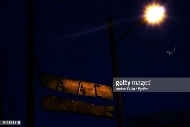 low angle view of illuminated signboard against sky at night - andres ruffo stock-fotos und bilder
