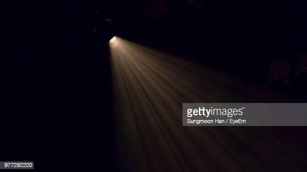 Low Angle View Of Illuminated Stage Light In Darkroom
