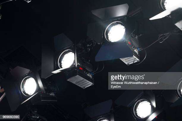 low angle view of illuminated stage lights - television studio stock pictures, royalty-free photos & images